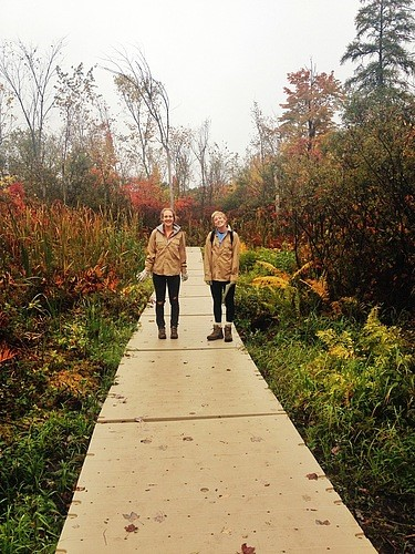 Two Kalamazoo College students standing on the wetland boardwalk
