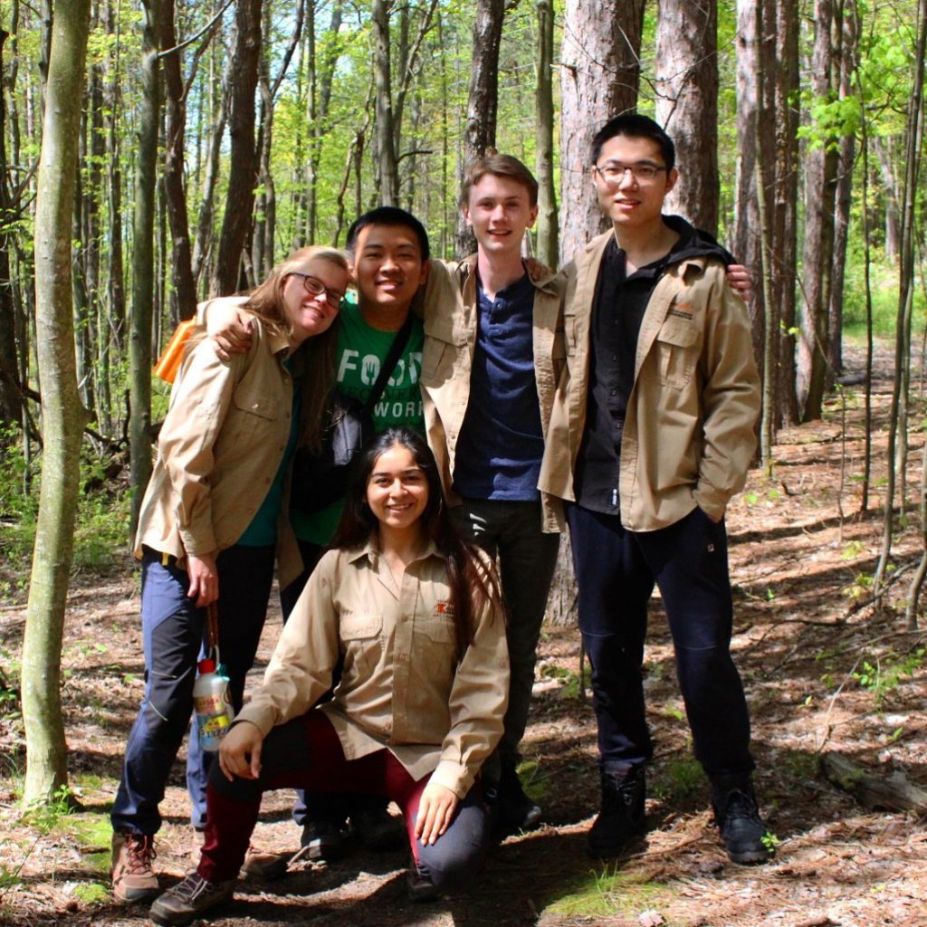 Group of students in the woods while wearing Lillian Anderson Arboretum work shirts