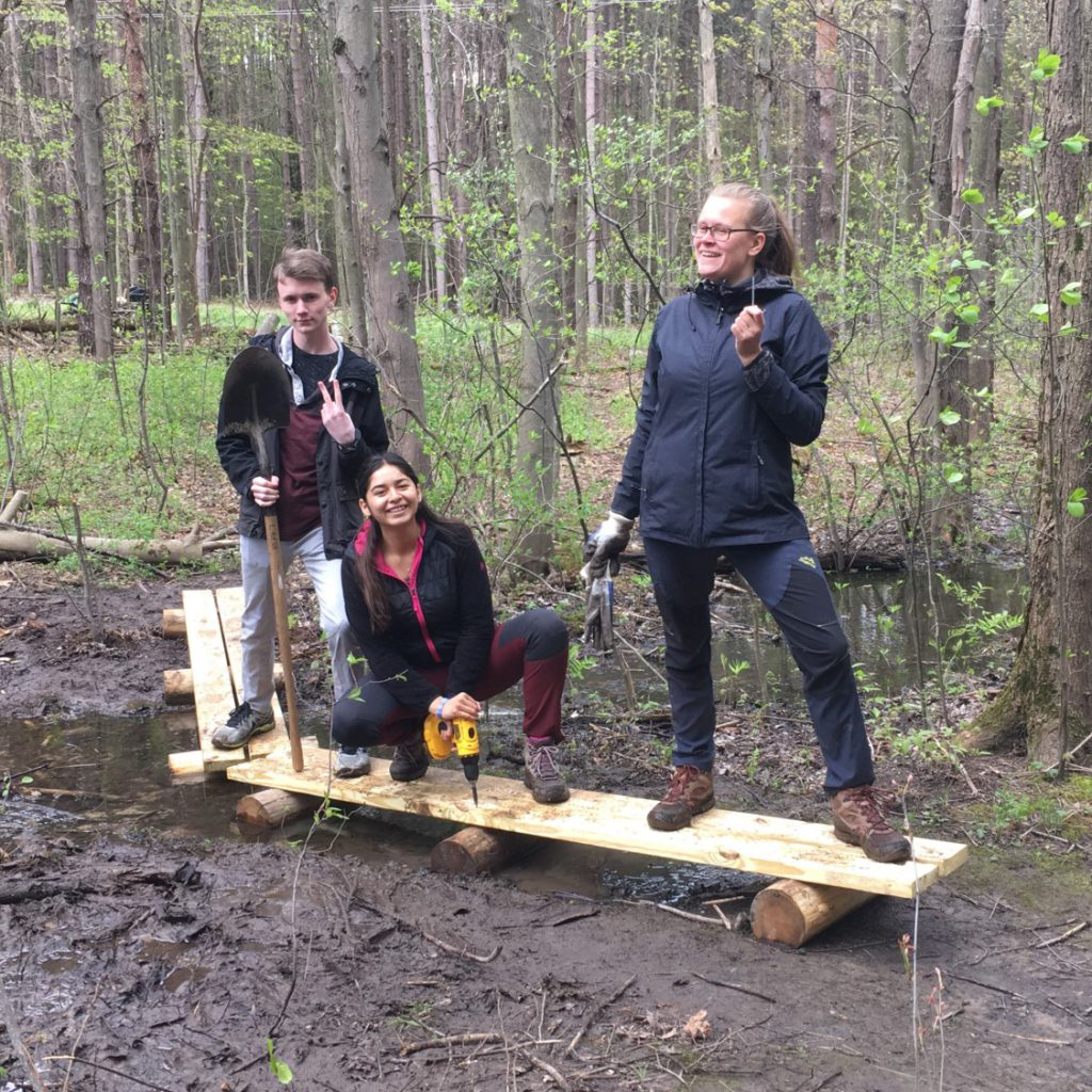 Three students taking a break while building a foot bridge over a muddy path